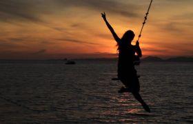 夏日海边黄昏日落秋千摆动入镜高清实拍