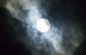 黑暗夜空云雾朦胧笼罩着圆月