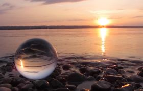 黄昏日落下的海边石头上一个透明球