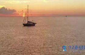 美好日落时飞过海面帆船波纹荡漾壮观自然高清实拍视频素材