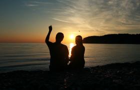 浪漫的情侶日落時坐在海邊的沙灘上約會視頻素材