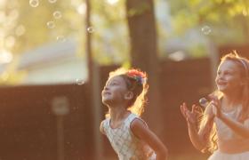 近距離拍攝?兩個外國小女孩跳著捉天空中的泡泡視頻素材