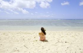女子坐在沙滩上吹海风看大海视频素材
