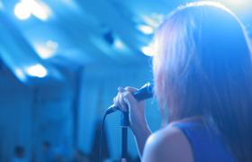 近距离拍摄一位女性在灯光闪耀下唱歌视频素材