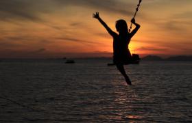 日出海水波光粼粼女子海边荡秋千实拍视频