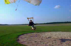 實拍跳傘女性歡快著陸草地高清視頻素材下載