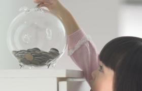 慢动作拍摄小女孩蹒跚踮脚投放硬币实拍视频素材