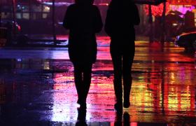 夜晚霓虹燈光映射在被雨淋濕的街道人流車流實拍視頻素材