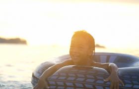戴着游泳圈的小男孩在海边欢乐戏水美好人物生活实拍视频