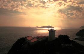 海面光輝閃爍岬角燈塔日落風景HD航拍視頻