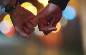 繁华夜晚城市街头幸福恋人拉手逛街手部动作特写视频