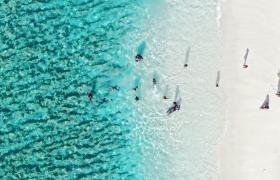 美丽纯净白沙海滩人们嬉戏游泳HD航拍视频素材