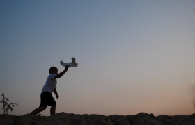 落日下小男孩手举着飞机奔跑的剪影MOV实拍视频