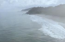 朦胧雾气笼罩海水翻滚推向沙滩移动航拍高清视频