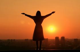 橙色夕阳光辉下女子站在高处张开手臂拥抱生活主题高清实拍视频