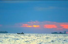 美麗夕陽光輝漁船剪影海面飄蕩日落美景實拍視頻