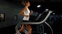 外国女士在跑步机上跑步健身运动