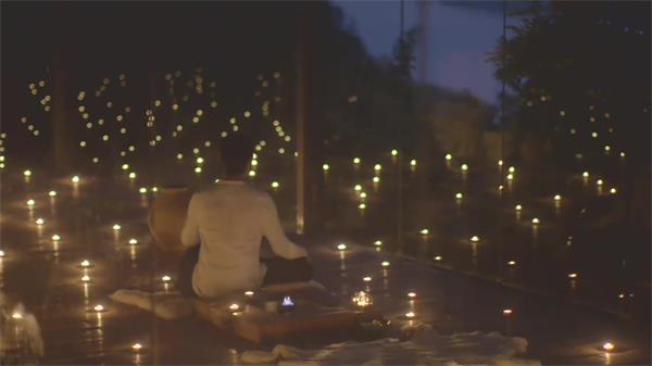空中充满烛炬男士坐在地板默坐考虑烛光点亮整个房间高清视频实拍