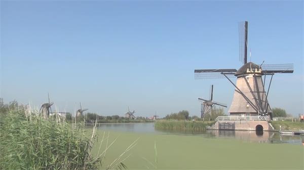 柔美欧式情况草丛河道边微风车旋转风力发电景点高清视频实拍