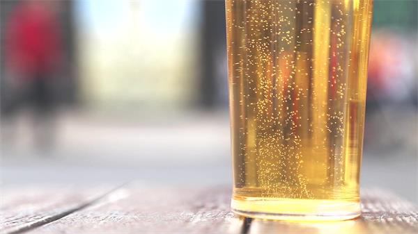街头拍摄装满啤酒杯子摆放桌子上泡沫飘浮啤酒形象宣传高清实拍