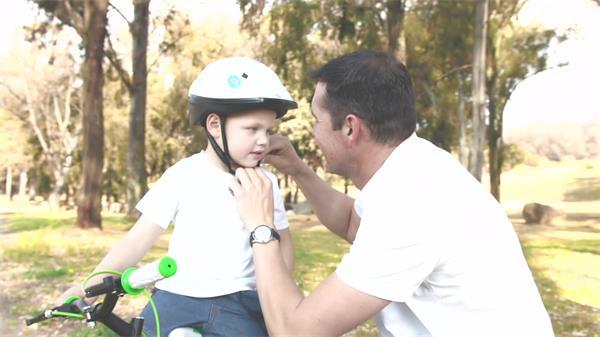 日落黄昏父子公园中欢乐骑单车穿戴头盔防护安全措施高清视频实拍