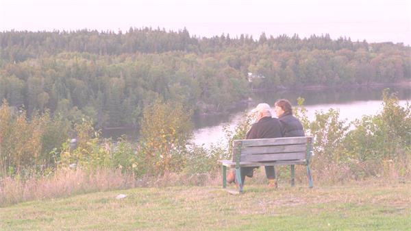 恩爱夫妻在山上椅子享受湖边自然风光镜头高清视频实拍