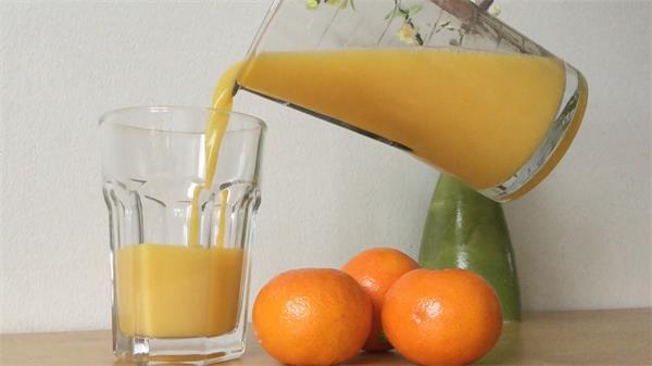 新鲜橙子榨汁橙汁倒进透明杯子食品展示镜头高清视频实拍