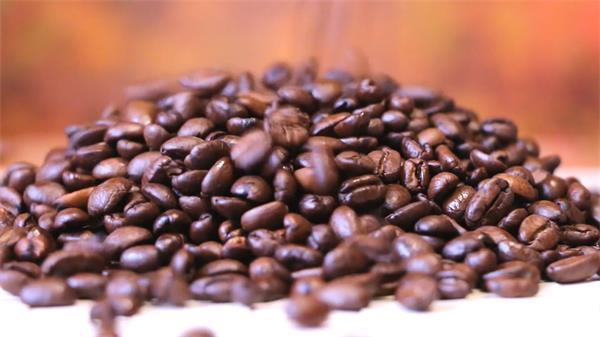 烘培后表面?#22303;?#26837;色咖啡豆倒进桌面散落滑动特写高清视频实拍