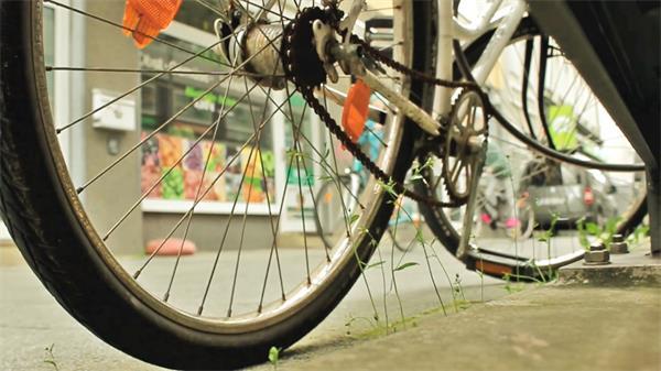 ?#32321;?#33258;行车停放轮胎框架铁链特写路上人们骑行高清视频拍摄