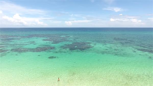一望无际清澈蔚蓝海洋水清沙幼男人行走海上航拍高清视频实拍