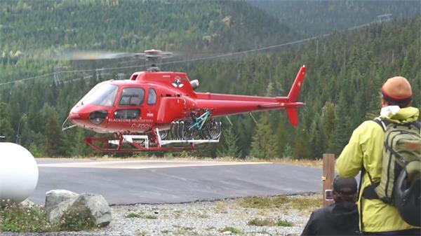 红色多功能直升机高山盘旋路面运输高清视频实拍
