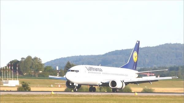 大型飞机穿过群山快速稳当降落跑道滑动停机坪飞机降落高清视频实