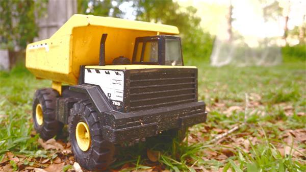 陽光燦爛戶外森林公園草地擺放一輛兒童玩具卡車鏡頭特寫延時高清