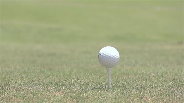 休闲生活阳光照耀草坪上高尔夫球场打高尔夫球进球洞动态高清视频