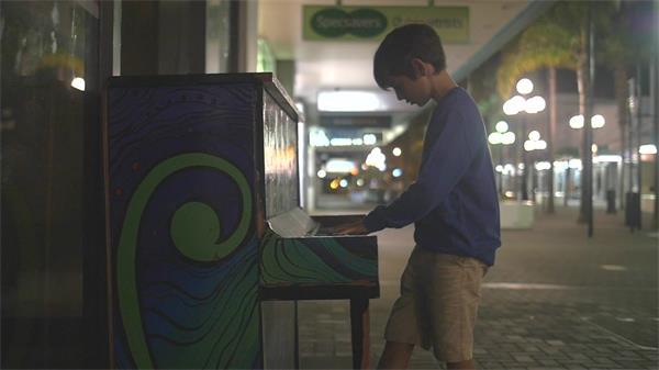 繁华城市建筑夜景灯光明亮?#20540;?#30007;孩弹钢琴镜头高清视频实拍