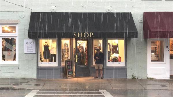 倾盘大雨服装店门口人们停留门前避雨生活景象高清视频实拍